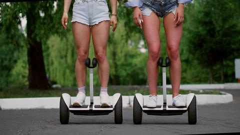 Close-up of two girls in short shorts on a self-balancing scooter go straight to Live Action