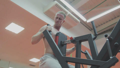 A muscular man with a naked torso trains on a fitness machine in a fitness club Live Action