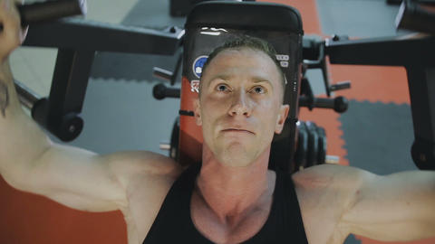 A muscular man in a black T-shirt is training on a fitness machine in a fitness Footage
