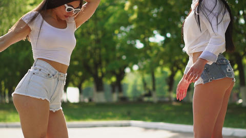 Two girlfriends in short denim shorts and white t-shirts are having fun on a Footage