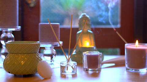Aromatherapy table setting with perfumed candles, oil burner, buddha, and mood Footage