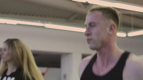 A man and a girl are training on a treadmill in a fitness club Footage