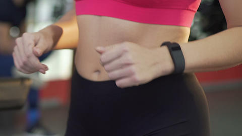 Sporty female walking on treadmill, smart watch on wrist, tracking application Footage