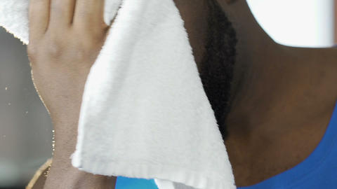 Attractive guy wiping face with towel after training in gym, looking at camera Footage