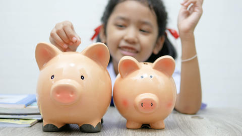 Asian little girl in Thai student uniform putting coin in to piggy bank shallow depth of field Live Action