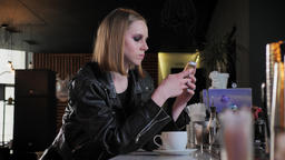 Young beautiful women in black jacket with heavy make up sitting and chatting on Footage