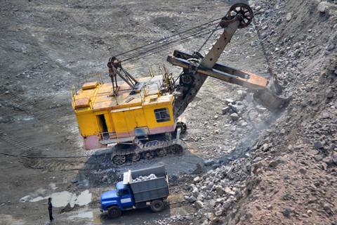 huge excavator and truck on granite quarry Fotografía