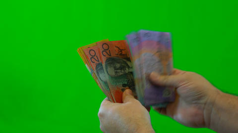 Mans hands counting Australian money, close up against green screen Footage