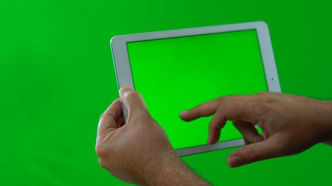 Man using and typing on tablet device against green screen, to the side ビデオ