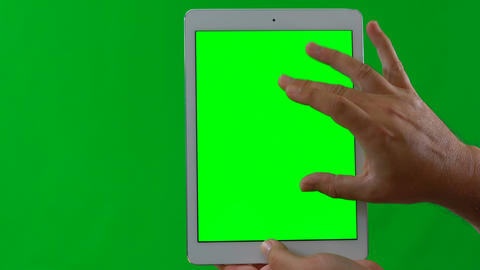 Man using tablet device, swiping and touching, front facing against green Live Action