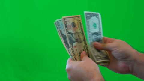 Mans hands closeup, counting United States money, against green screen Footage
