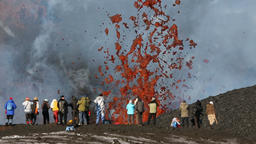 Travelers take pictures fountain of flying red hot lava, erupting from volcano GIF