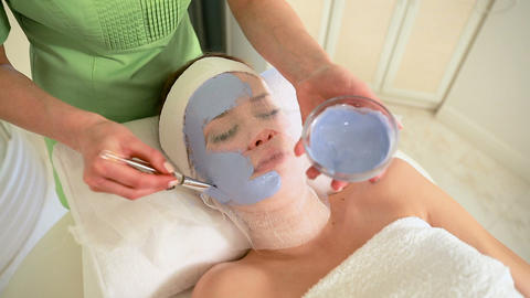 Young beautiful woman in a blue mask for the face. Spa treatment Footage