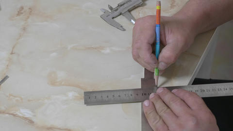 Male hands measuring width knife blade during manufacture in production hall Live Action