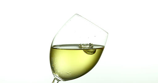 Drop of White Wine falling into Glass, against White Background, Slow motion 4K Footage