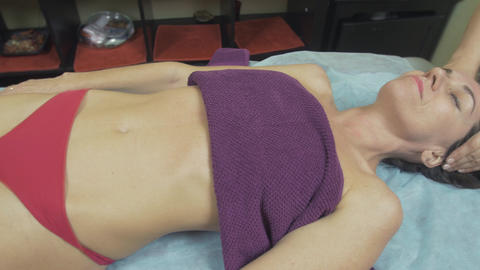 Masseuse make relaxing massage of head to young slim smiling woman in saloon Footage
