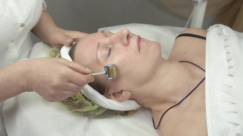 Cosmetologist make galvanotherapy face of adult woman in beauty saloon Live Action