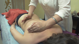 Masseuse make therapeutic massage of back, shoulders to young woman in saloon Footage