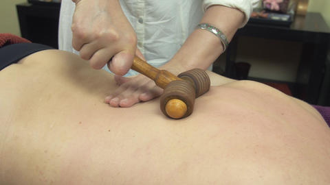 Masseuse make therapeutic massage of backbone by wooden massage roller to woman Footage