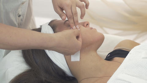 Cosmetologist remove waxing strip out cheeks of girl in beauty saloon. Epilation Live Action