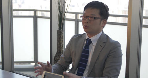 Japanese business man explains business concepts to colleagues Footage