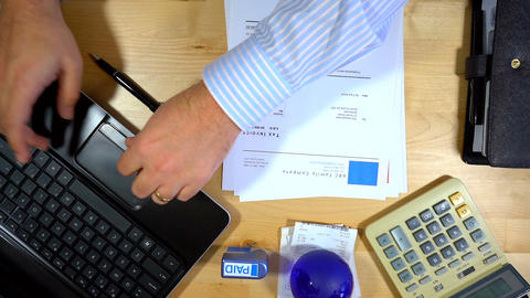 Accountant at desk overhead, paying invoices, real time Footage