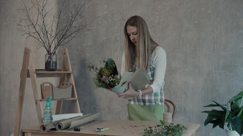Florist creating beautiful flower arrangement GIF
