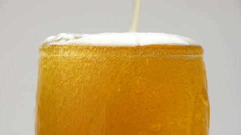 Close up pouring beer with bubbles in glass GIF