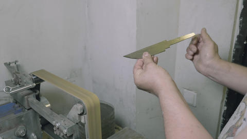Diy man looking at metal knife and grinding it on abrasive machine, partial view Footage