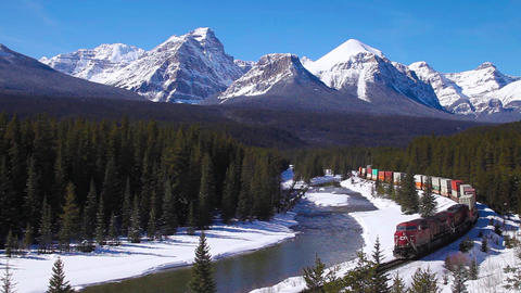 A very long freight train traveling through the mountains in Banff National Footage