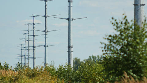 modern high voltage towers row against blue sky Footage