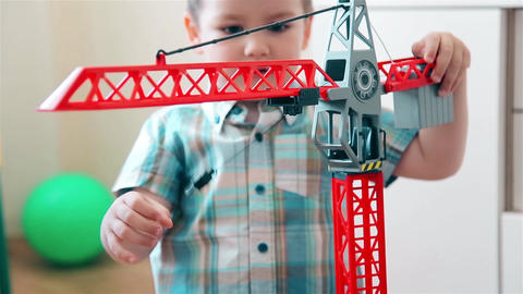 The child learns to lift and lower the load on the crane Footage