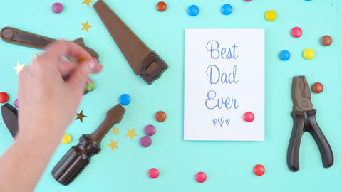 Happy Father's Day overhead of chocolate tool set with Best Dad Ever greeting Footage