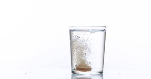 Tablet or Vitamin Falling and Dissolving into a Glass of Water against White Background, Slow Motion Footage