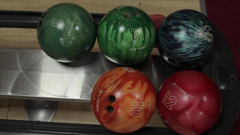 Colorful bowling balls are waiting to be selected.Bowling.A young man chooses a Footage