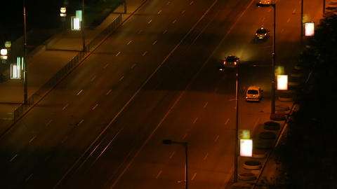 Wide city street at night with cars passing, vibrant life big city, time-lapse Footage