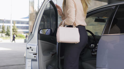 Beautiful lady boss getting into the car near business center, transport Live Action