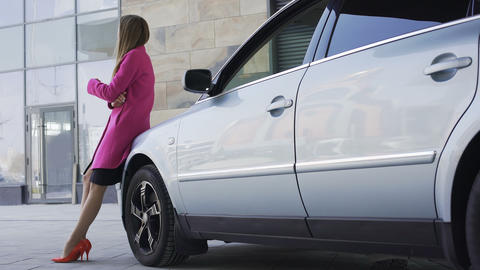 Pretty sad female standing near automobile and waiting for boyfriend, loneliness Footage
