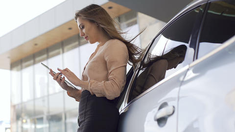 Pretty sales manager standing near car and working on tablet. Businesswoman Footage