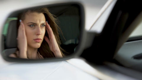 Beautiful woman sitting in car, suffering from terrible headache, unhappy Live Action