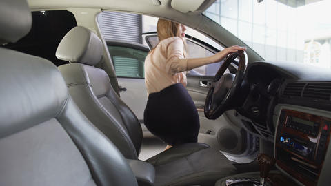Business woman getting into car and fastening her seat belt, transport for rent Footage