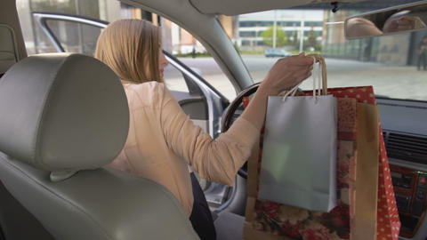 View of attractive business woman getting into car after shopping. Purchases Footage
