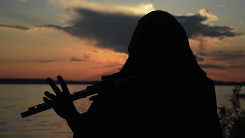 A man playing a flute at sunset Footage