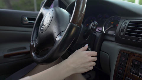Woman driver hand inserting car key and starting engine. Transportation. Closeup Footage