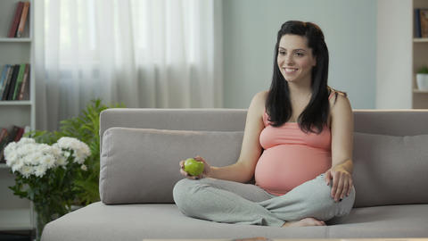 Pregnant lady taking care of child, living healthy lifestyle eating fresh fruits Live Action