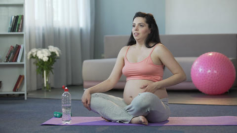 Lady in final stages of pregnancy doing yoga, drinking water, safe childbirth Footage