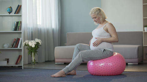 Happy future mother enjoying and rejoicing with pregnancy, gently stroking tummy Footage