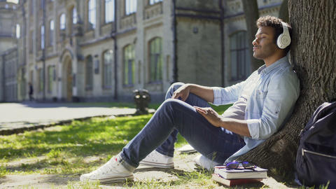 Mixed young male sitting under tree in headphones, eyes closed, enjoying music Footage