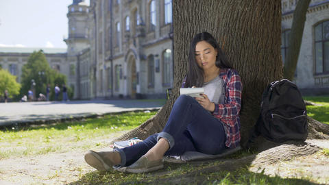Asian girl sitting under tree, writing fast in notebook, inspiration, poetry Footage