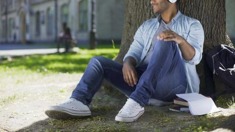 Multiracial male in headphones sitting under tree, listening to favorite music Footage